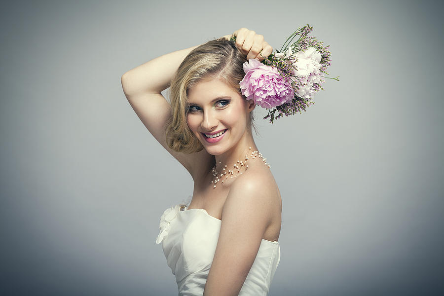 Blond bride holding bouquet of pink flowers Photograph by Yulia-Images