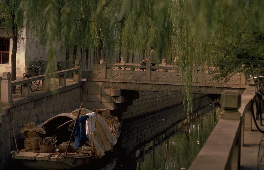 Boat In Canal Against Footbridge Photograph by Michel Guntern / EyeEm