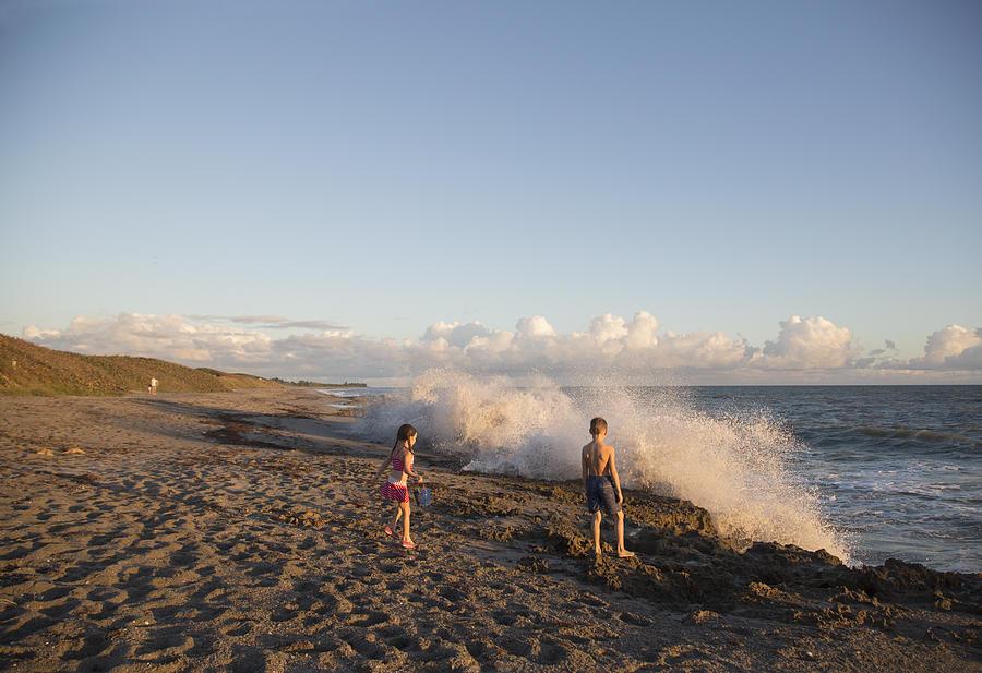 Boy And Sister Watching Splashing Waves From Beach, Blowing Rocks Preserve, Jupiter Island, Florida, Usa Photograph by Kinzie Riehm