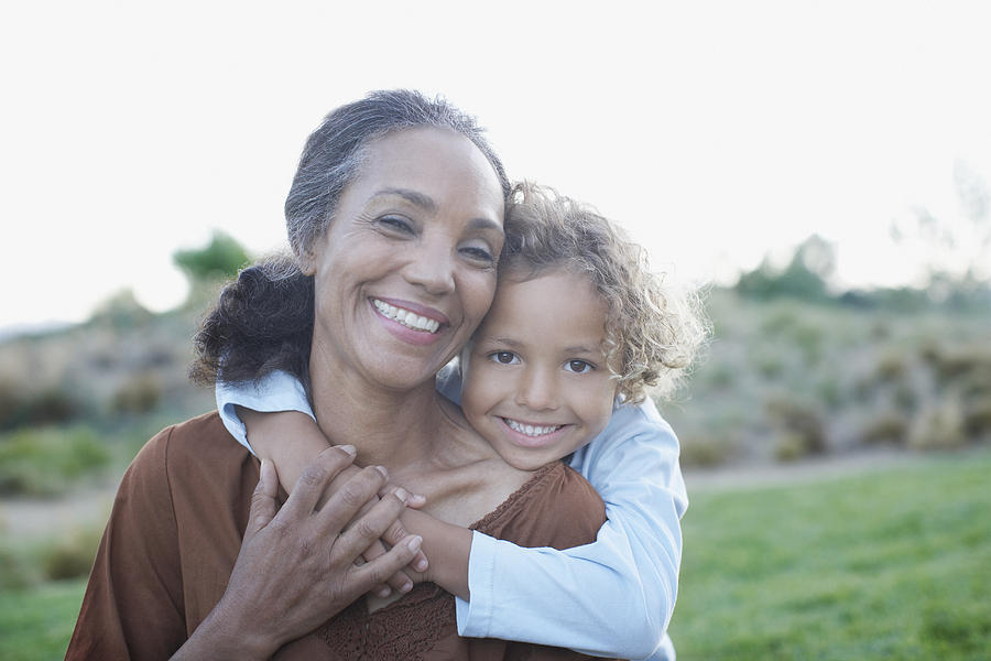 Boy hugging grandmother Photograph by Tom Merton
