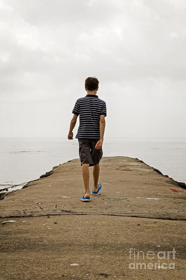 Beach Photograph - Boy Walking On Concrete Beach Pier by Edward Fielding