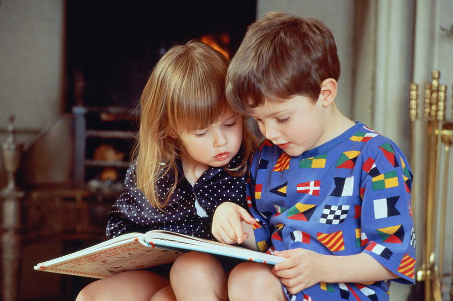 Boy(4-5)and girl(2-3)sat by fire in pyjamas reading book together Photograph by Bob Thomas