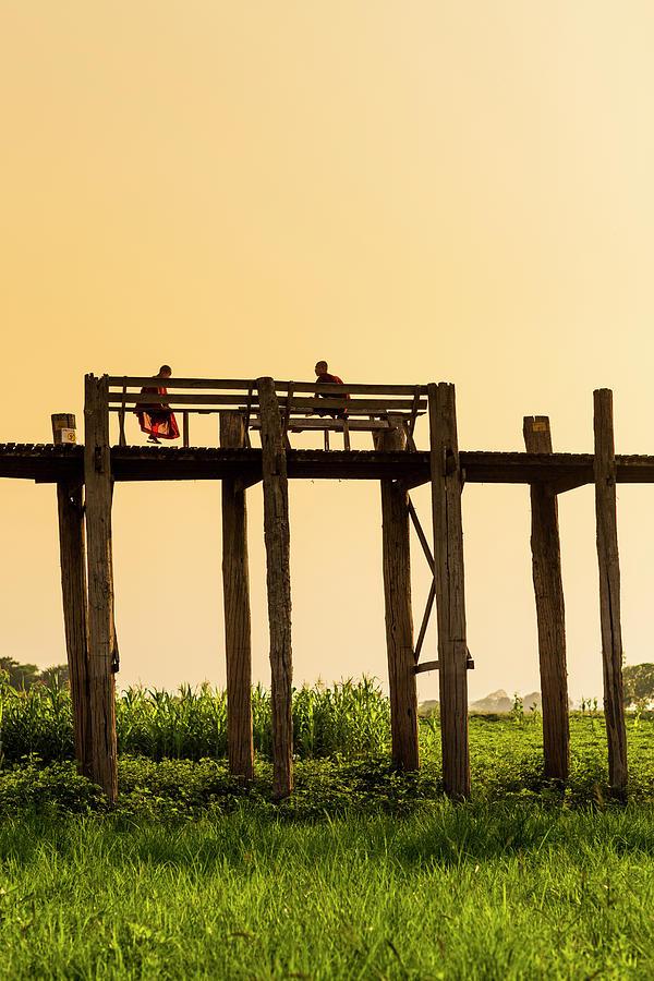 Buddhist Monks Seated On U Bein Bridge Photograph by Merten Snijders