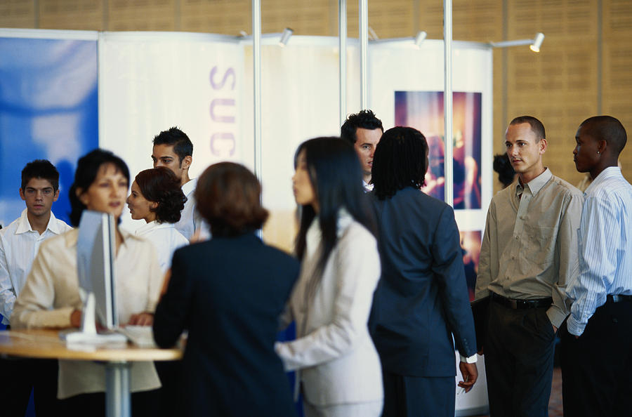 Business executives standing in exhibition hall Photograph by Stockbyte