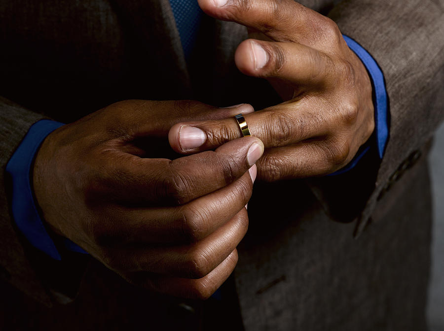 Business man putting on wedding band Photograph by Le Club Symphonie