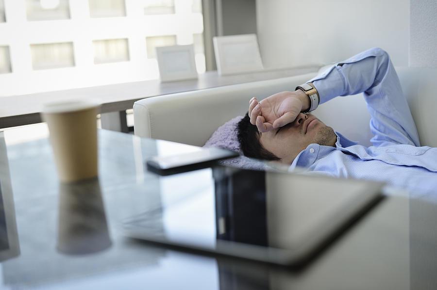 Business Man Sleeping On The Sofa In Office Photograph by Yagi Studio