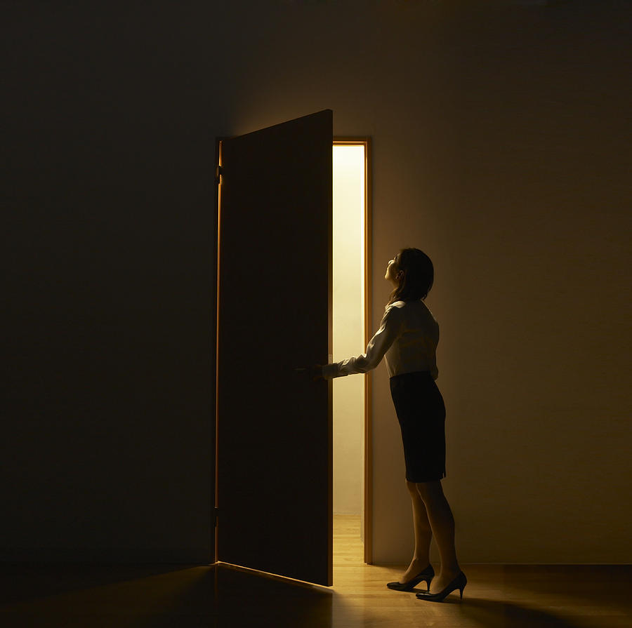 Business Woman Opening  Door Standing In Light Photograph by D-base