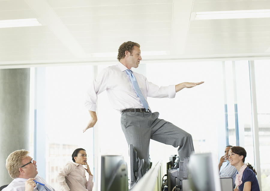 Businessman dancing on cubicle desk Photograph by Paul Bradbury
