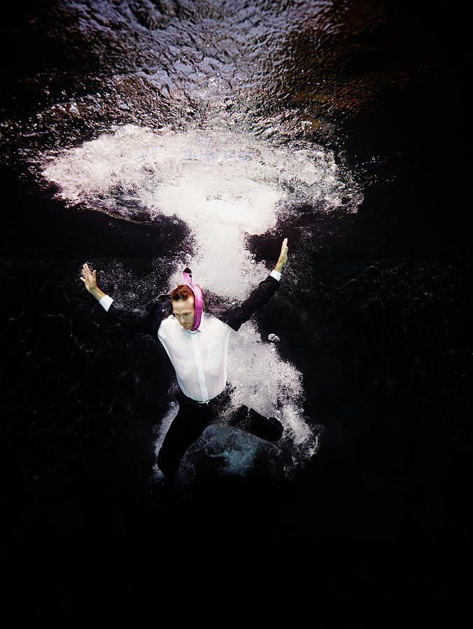 Businessman In Suit Plunging Into Water Photograph by Thomas Barwick