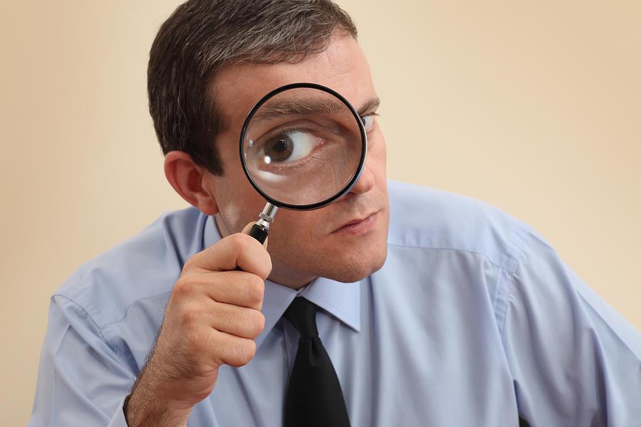 Businessman looking at camera through a magnifying glass Photograph by Mgkaya