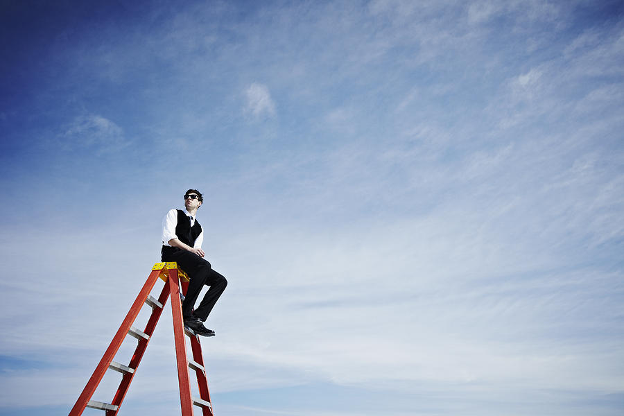 Businessman sitting on top of ladder looking out Photograph by Thomas Barwick