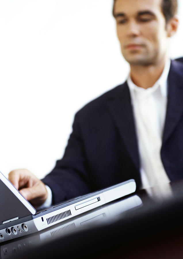 Businessman Using Laptop Computer Photograph by Vincent Hazat