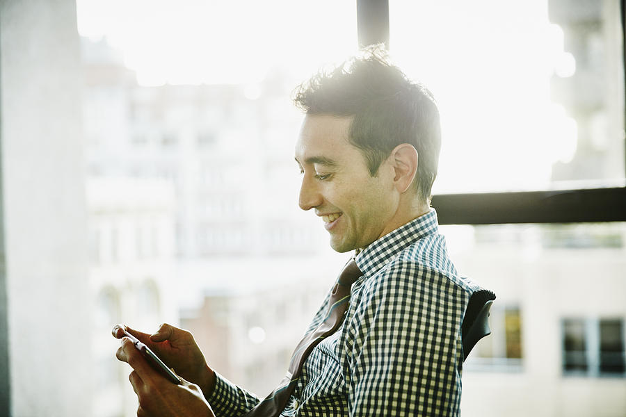 Businessman working on smartphone in office Photograph by Thomas Barwick