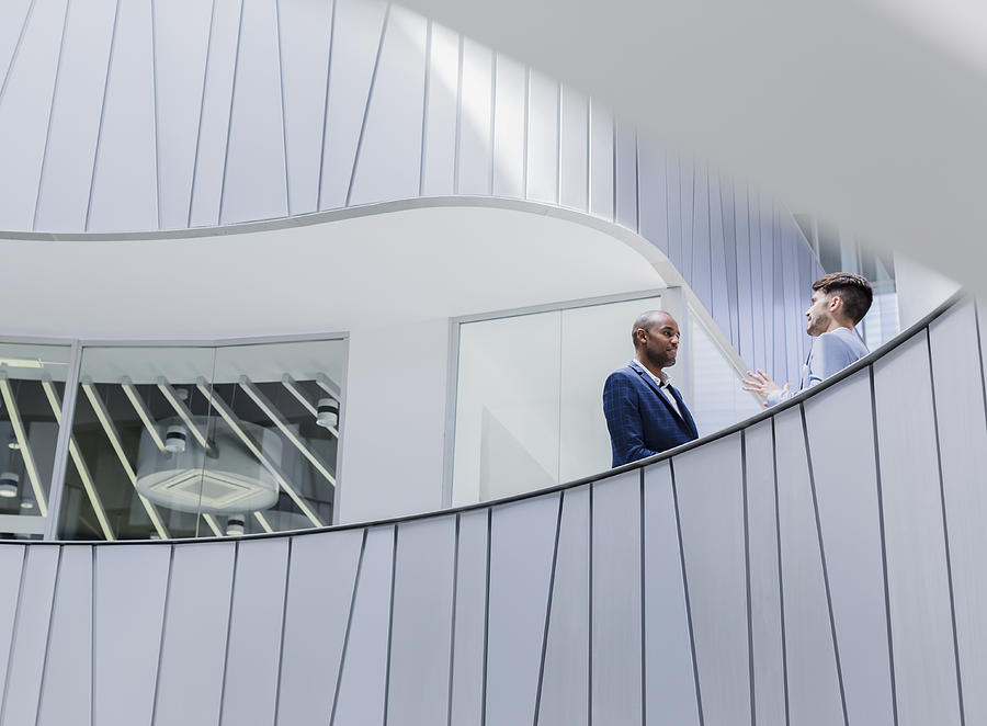 Businessmen Talking On Architectural, Modern Office Balcony Photograph by Caiaimage/Martin Barraud