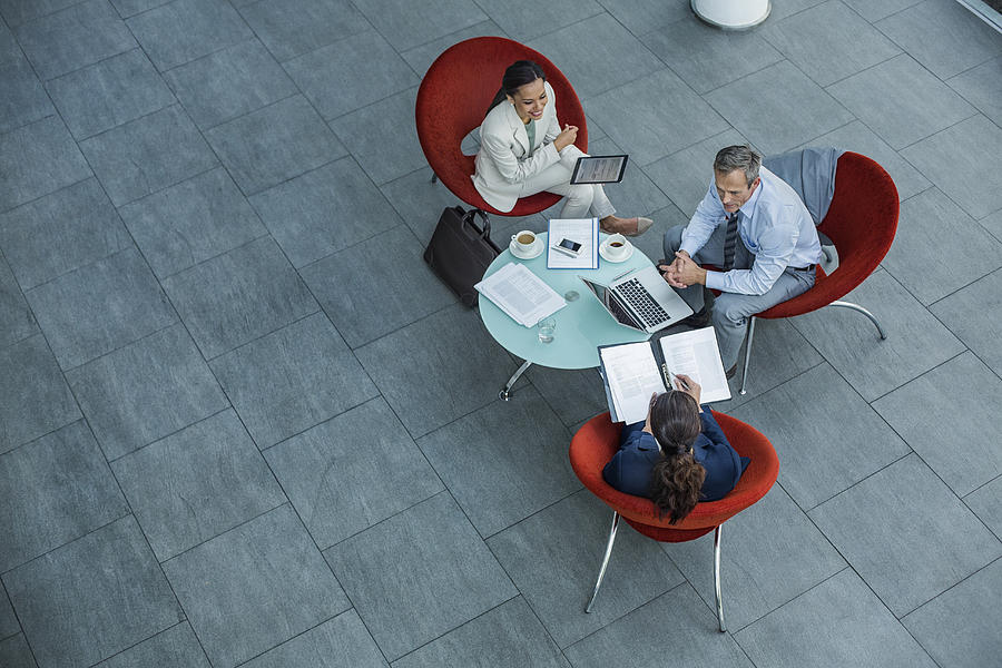 Businesspeople discussing strategy at coffee table Photograph by Morsa Images
