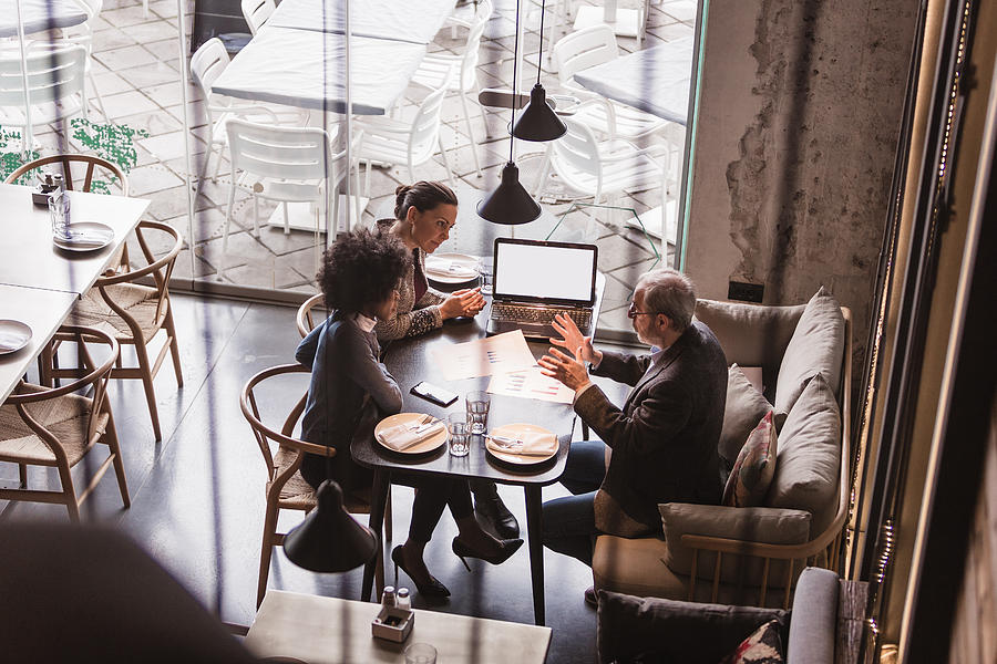 Businesspeople Having Meeting In A Restaurant. Photograph by NoSystem images
