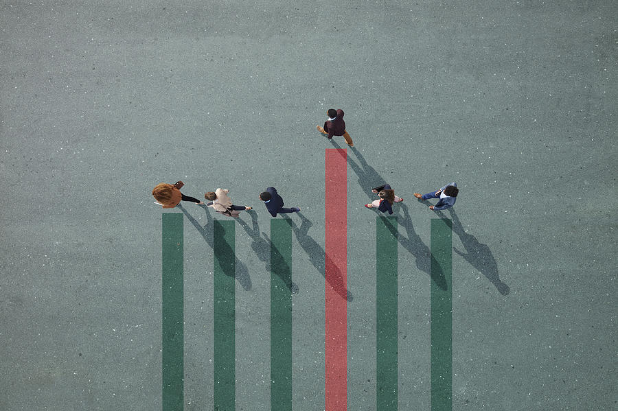 Businesspeople walking in line on bar chart painted on asphalt, one person walking off. Photograph by Klaus Vedfelt
