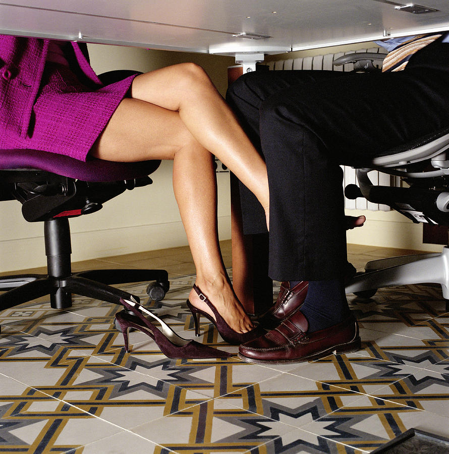 Businesswoman rubbing foot against businessmans leg, low section Photograph by Andy Sotiriou