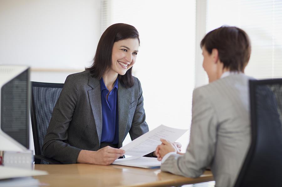 Businesswomen with paperwork talking face to face Photograph by Robert Daly