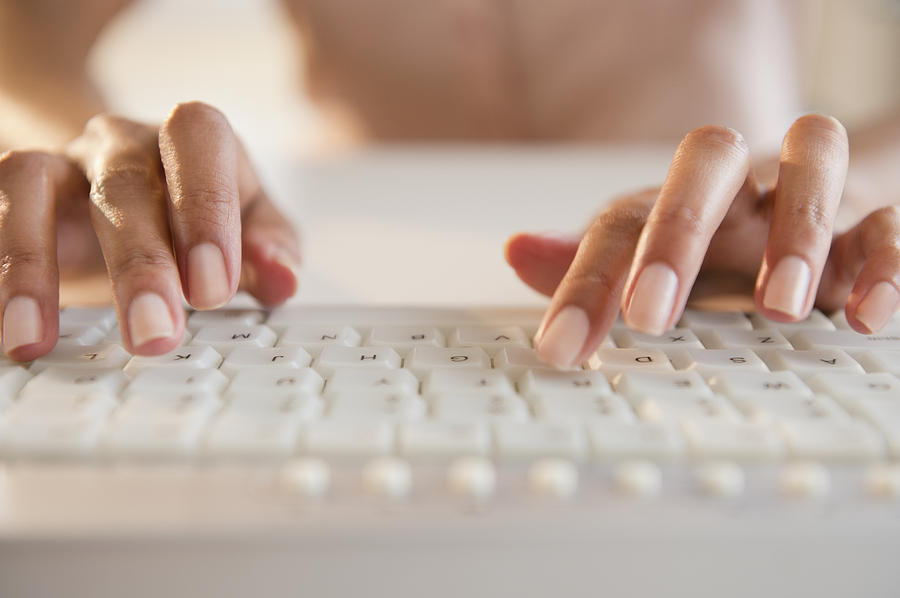 Cape Verdean woman typing on keyboard Photograph by Blend Images - JGI/Jamie Grill