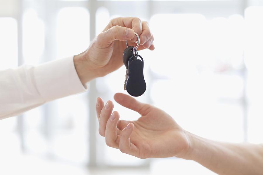 Car salesman handing keys to customer Photograph by Photo_Concepts