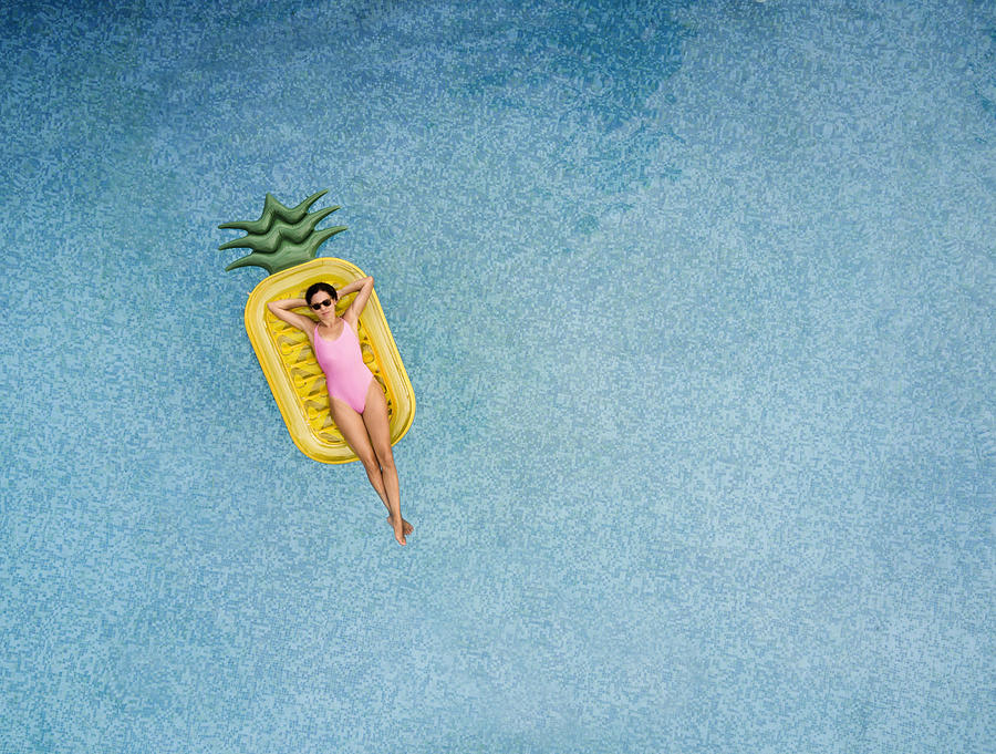 Carefree woman on inflatable pineapple Photograph by Orbon Alija