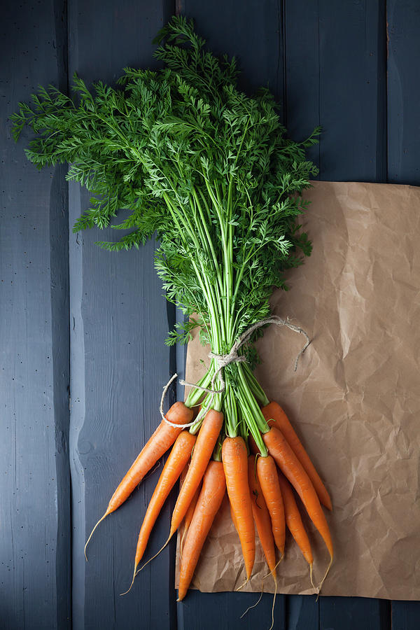Carrots With Brown Paper On Wooden Photograph by Westend61