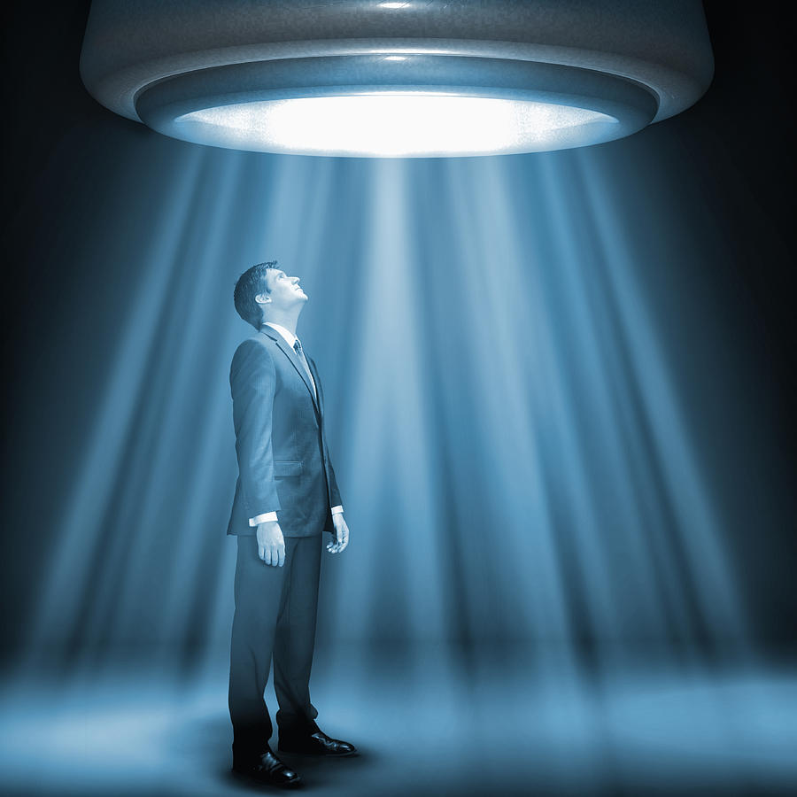 Caucasian businessman standing underneath glowing lights Photograph by Jacobs Stock Photography Ltd