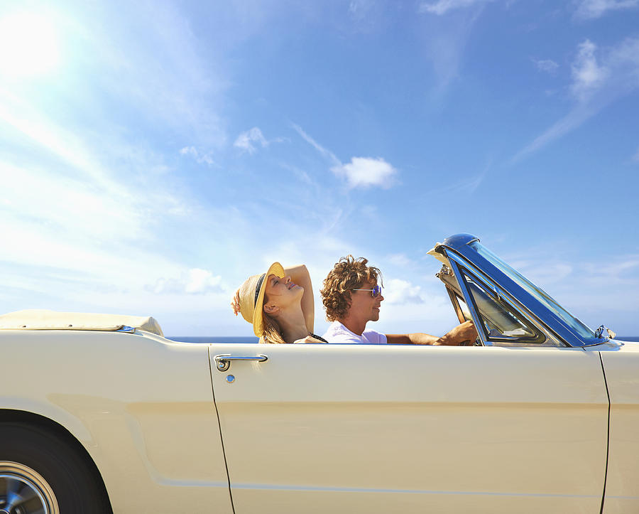 Caucasian couple driving convertible under blue sky Photograph by Colin Anderson Productions Pty Ltd