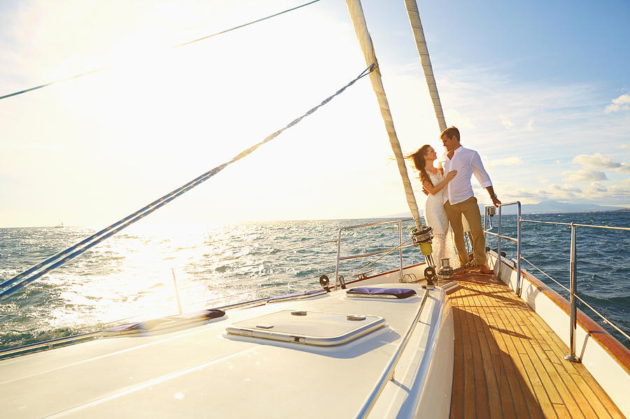 Caucasian couple hugging on yacht deck Photograph by Colin Anderson Productions pty ltd