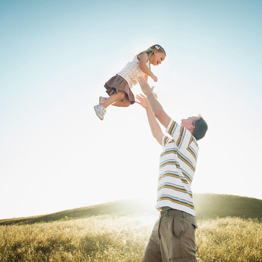 Caucasian Father Lifting Daughter Photograph by Erik Isakson