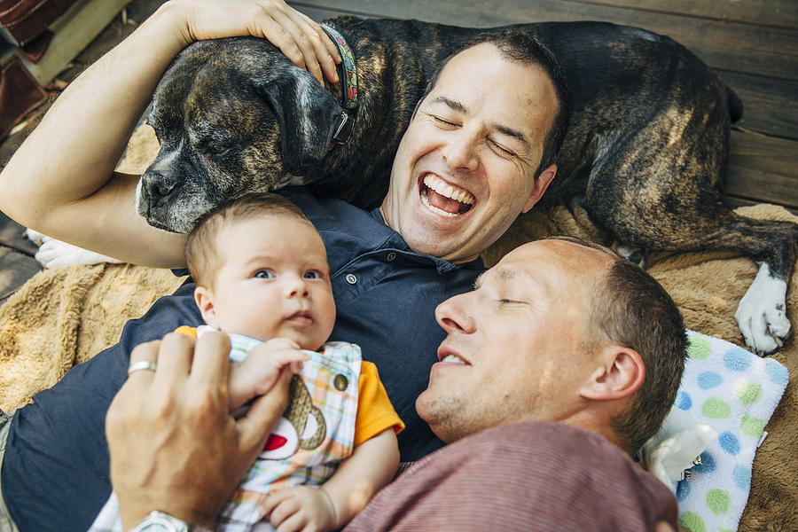 Caucasian gay couple cuddling baby boy and dog Photograph by Inti St Clair