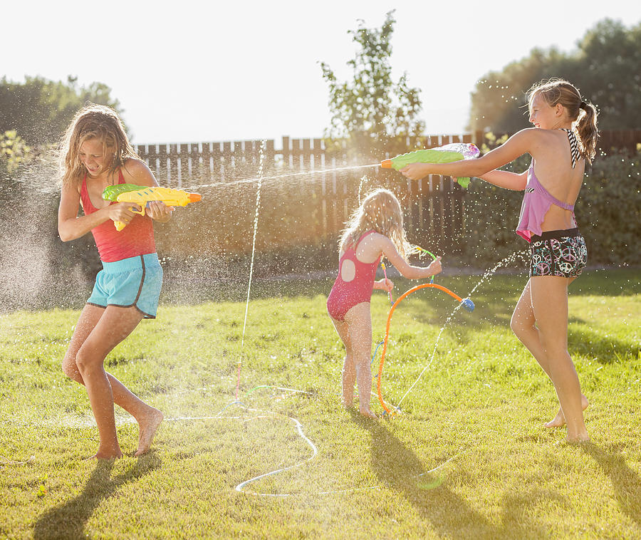 Caucasian Girls Shooting Water Guns Photograph by Blend Images - Mike Kemp