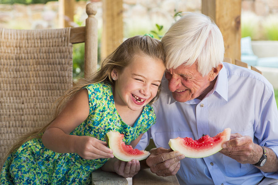 Caucasian man and granddaughter eating watermelon Photograph by Marc Romanelli