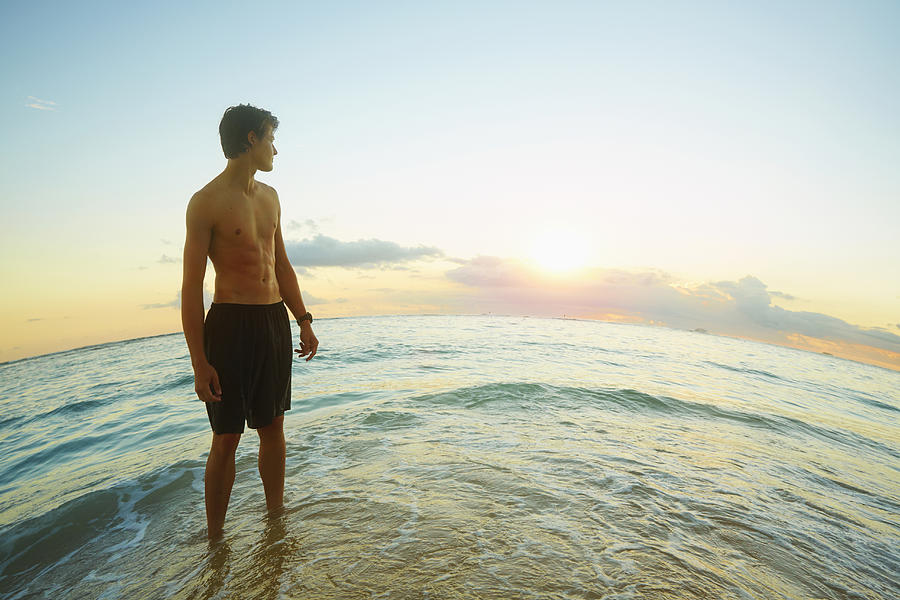 Caucasian teenage boy standing on beach Photograph by Colin Anderson Productions pty ltd