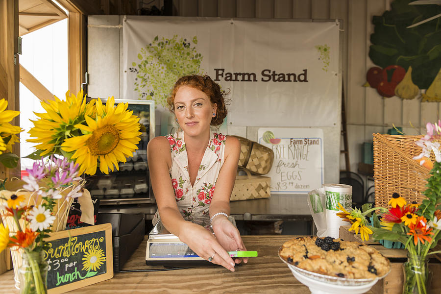 Caucasian woman selling fruit crumble and flowers at farmers market Photograph by Mark Edward Atkinson