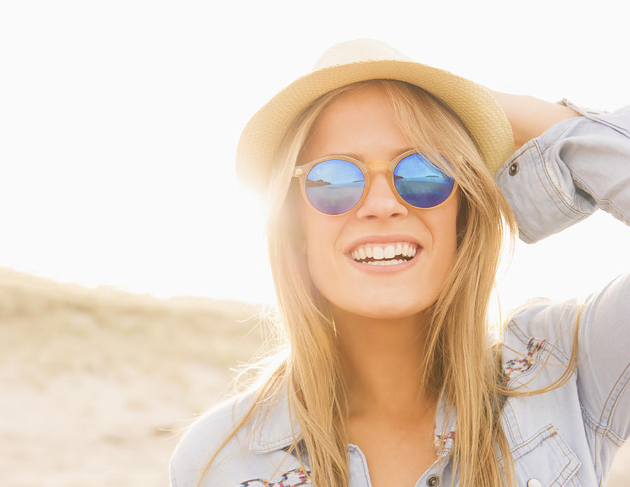 Caucasian woman wearing hat and sunglasses on beach Photograph by Jacobs Stock Photography Ltd