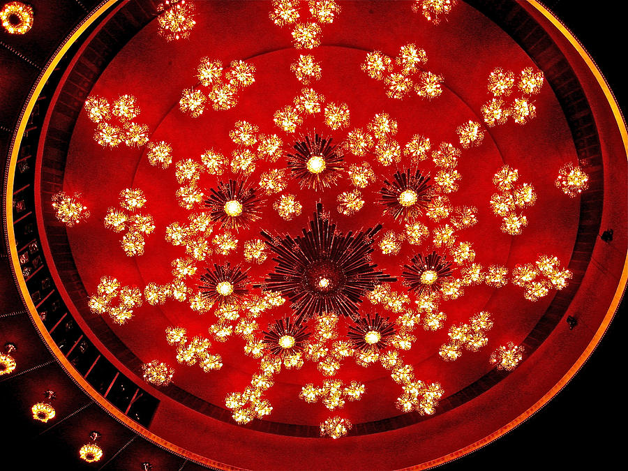 A red circular ceiling design with dozens of small crystal lights and an abstract black star in the center