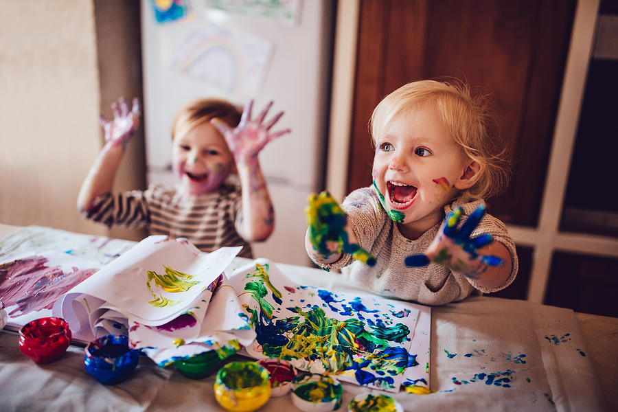 Cheerful little children having fun doing finger painting Photograph by Wundervisuals