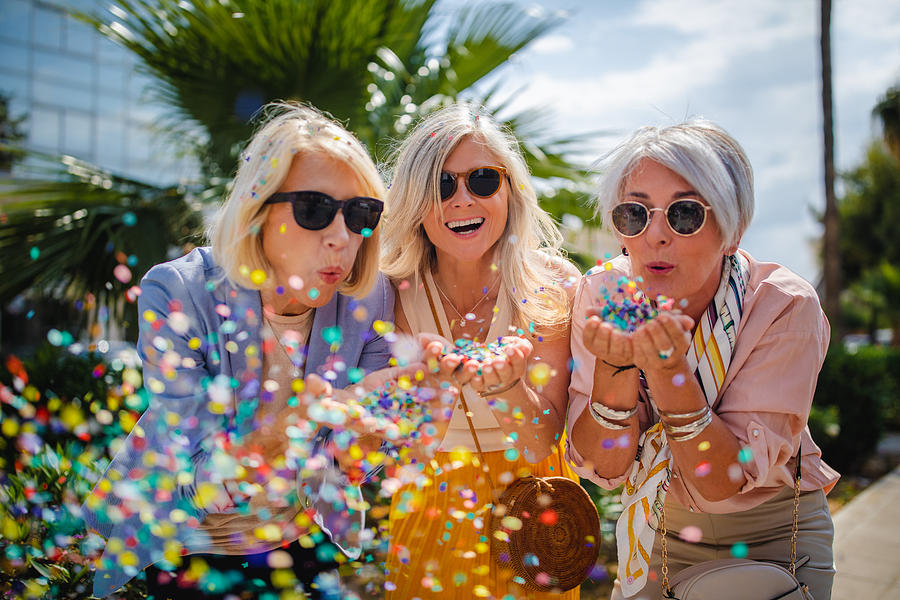 Cheerful senior women celebrating by blowing confetti in the city Photograph by Wundervisuals