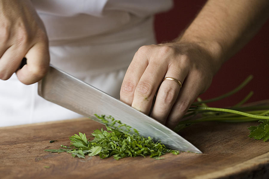 Chef chopping parsley Photograph by Image Source