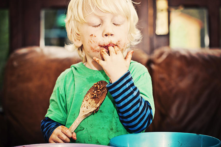 Child enjoying eating chocolate Photograph by Sally Anscombe