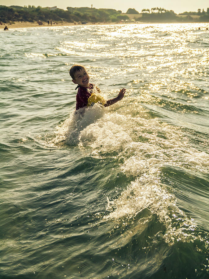 Child Paly With Waves Into The Sea Photograph by Alexd75
