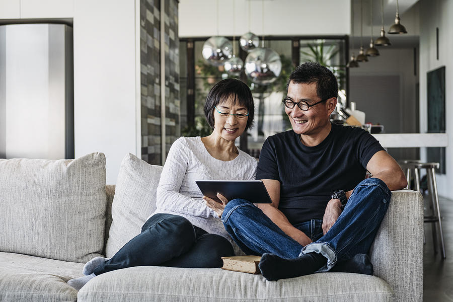 Chinese couple on sofa watching movie online Photograph by JohnnyGreig
