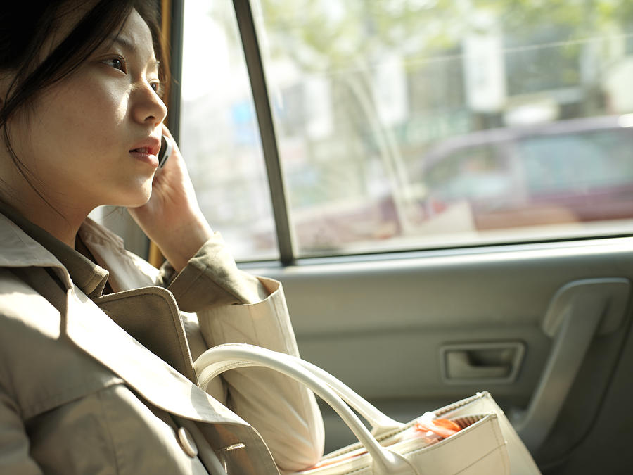 Chinese Woman Using Mobile Phone In Car by xPACIFICA
