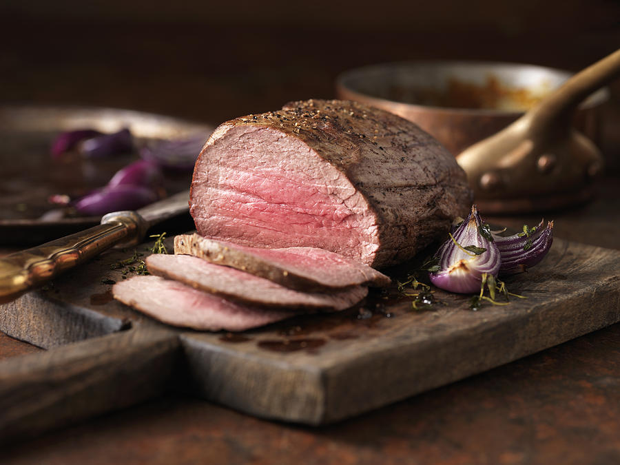 Christmas dinner. Chateaubriand steak cooked with a thick cut from the tenderloin filet, rare medium served with roasted onions, pepper and herbs Photograph by Diana Miller
