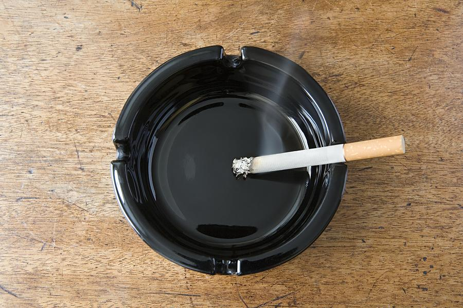 Cigarette burning Photograph by Image Source
