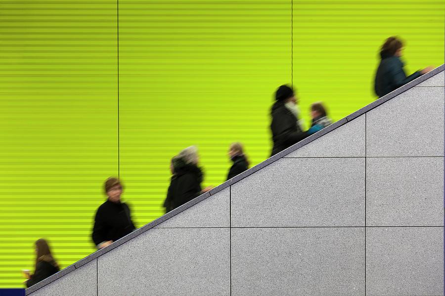 Civilians Riding An Escalator With A Photograph by Sebastian-julian