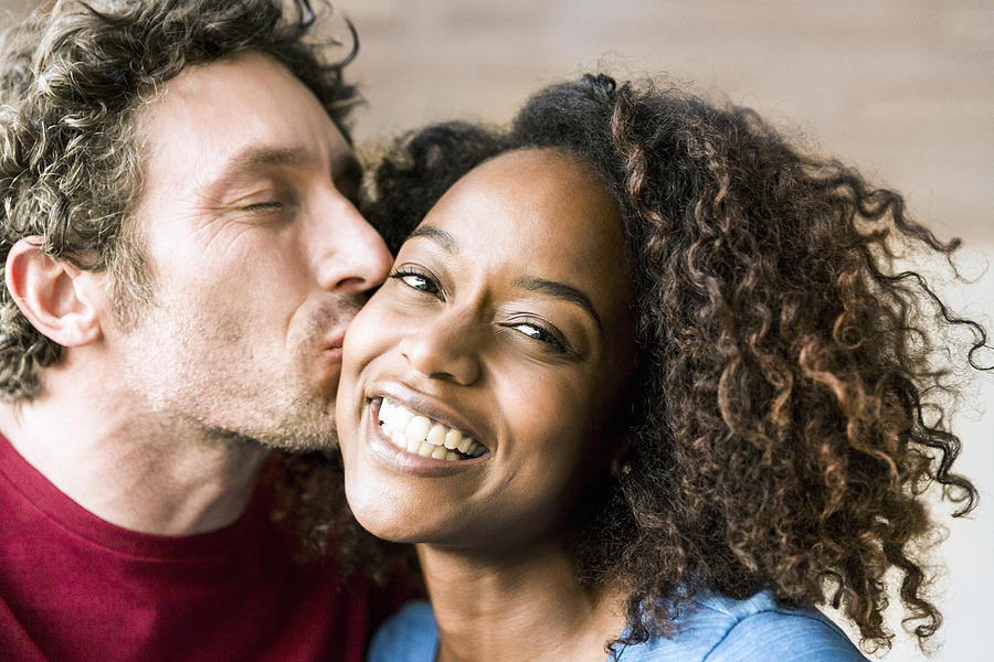 Close-up of man kissing cheerful woman on cheek Photograph by Portra