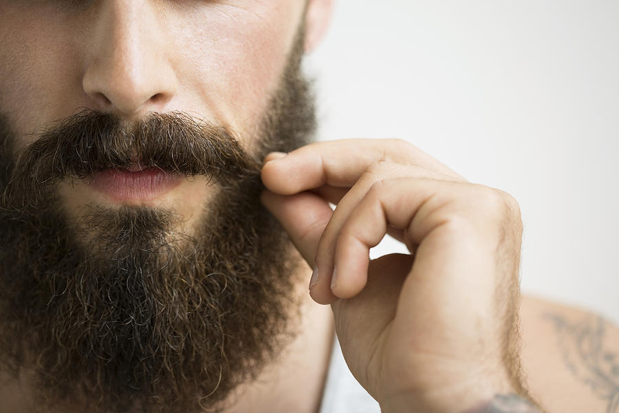 Close Up Of Man Touching Mustache Photograph by Hero Images